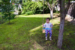 Petite fille dans l'oscillation en bois Image libre de droits