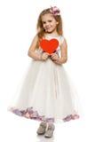Petite fille dans la belle robe retenant la forme de coeur Image stock