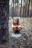 Petite fille dans la forêt de pin près de la bouteille en plastique images libres de droits