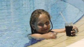 Petite fille dans la piscine avec la boisson froide banque de vidéos