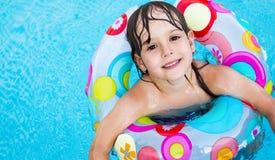 Petite fille dans la piscine avec la boucle de flotteur photographie stock