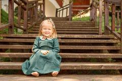 Petite fille dans la rétro robe de toile de vintage nu-pieds se reposant et souriant sur escaliers en bois en parc Photos stock
