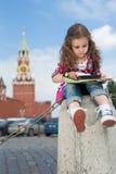 Petite fille dans la robe élégante se reposant sur le béton Image libre de droits