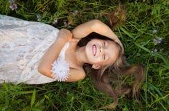 Petite fille dans la robe blanche se situant dans l'herbe et les rires Photo libre de droits