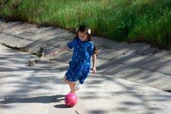 Petite fille dans la robe bleue donnant un coup de pied le ballon de football dans le drain de tempête photos stock