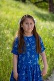 Petite fille dans la robe bleue faisant le visage inquiété ou dégoûté devant le champ vert photos stock