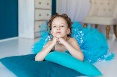 Petite fille dans la robe bleue se trouvant sur le plancher Image stock