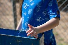 Petite fille dans la robe bleue utilisant le poste d'eau potable photo stock