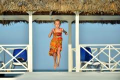 Petite fille dans la robe colorée sautant et dansant sur le pilier en bois blanc Photos libres de droits