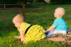 Petite fille dans la robe et le garçon jaunes dans la chemise bleue rampant sur l'herbe images libres de droits
