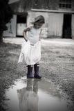 Petite fille dans la robe et le Wellies Photographie stock