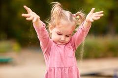 Petite fille dans la robe rose jouant avec le sable photographie stock libre de droits