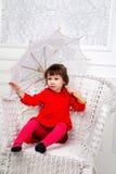 Petite fille dans la robe rouge dans le studio avec le parapluie Image libre de droits