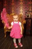 Petite fille dans la robe rouge restant avec la clavette rouge Photographie stock libre de droits