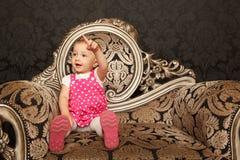Petite fille dans la robe rouge se reposant sur le rétro fauteuil Image libre de droits