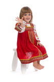 Petite fille dans la robe traditionnelle rouge sur une chaise Photos stock