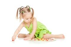 Petite fille dans la robe verte jouant le jeu de puzzle Images libres de droits