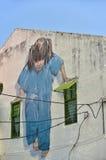 Petite fille dans le bleu sur le mur Photo stock
