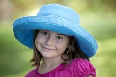Petite fille dans le chapeau bleu à l'extérieur Photo stock