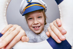 Petite fille dans le chapeau d'un capitaine regardant  Photos stock