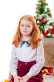Petite fille dans le chapeau de Santa près de l'arbre de Noël Photos libres de droits
