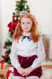 Petite fille dans le chapeau de Santa près de l'arbre de Noël Image libre de droits