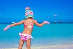 Petite fille dans le chapeau et des mitaines chauds sur la plage Photo stock
