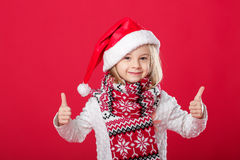 Petite fille dans le chapeau et l'écharpe de Santa sur le fond rouge Photographie stock libre de droits