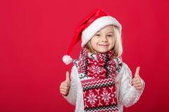 Petite fille dans le chapeau et l'écharpe de Santa sur le fond rouge Image stock