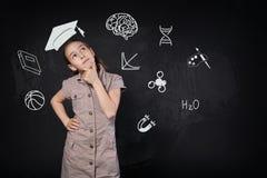 Petite fille dans le chapeau imaginaire d'obtention du diplôme pensant à l'école Photo stock