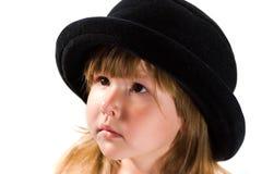 Petite fille dans le chapeau noir Image stock