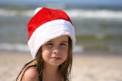 Petite fille dans le chapeau rouge le père noël sur la plage Photographie stock
