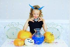 Petite fille dans le costume de démon jouant avec des potirons Images stock