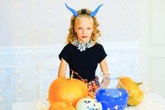 Petite fille dans le costume de démon jouant avec des potirons Images libres de droits