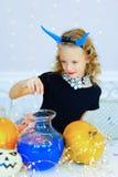 Petite fille dans le costume de démon jouant avec des potirons Photographie stock