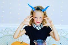 Petite fille dans le costume de démon jouant avec des potirons Image libre de droits