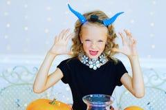 Petite fille dans le costume de démon jouant avec des potirons Photo libre de droits