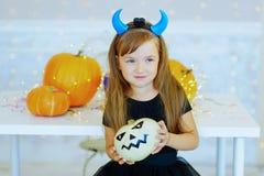 Petite fille dans le costume de démon jouant avec des potirons Photos libres de droits