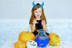 Petite fille dans le costume de démon jouant avec des potirons Photographie stock libre de droits