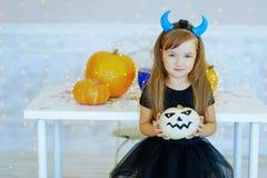 Petite fille dans le costume de démon jouant avec des potirons Photos stock