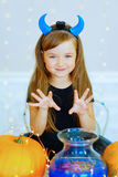 Petite fille dans le costume de démon jouant avec des potirons Photo stock
