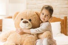 Petite fille dans le lit avec l'ours de nounours Photo stock