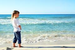 Petite fille dans le sable sur la plage Photo libre de droits