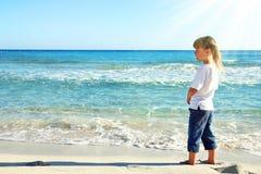 Petite fille dans le sable sur la plage Photo stock