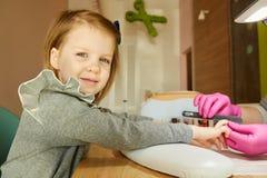 Petite fille dans le salon d'ongle recevant la manucure par l'esthéticien Petite fille atteignant la manucure le salon de beauté Images libres de droits