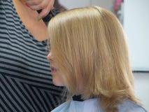 Petite fille dans le salon de coiffure Photos libres de droits