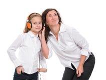 Petite fille dans les écouteurs et sa mère Photos stock