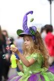 Petite fille dans les bulles de savon contagieuses de robe verte de fantaisie Photos stock
