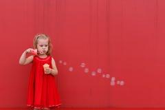 Petite fille dans les drtess rouges soufflant des bulles de savon sur le fond Photo stock