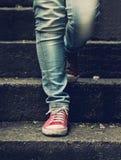 Petite fille dans les espadrilles rouges et des jeans se tenant sur les escaliers Photo stock